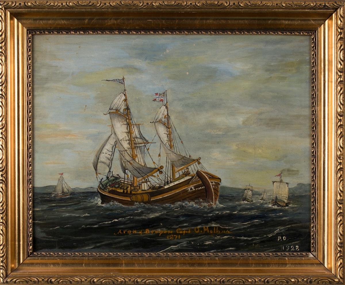 Skipsportrett av koff ARON med full seilføring. Ser andre mindre seilfartøy i bakbrunnen. Fører norsk handelsflagg med svensk-norsk unionsmerke.