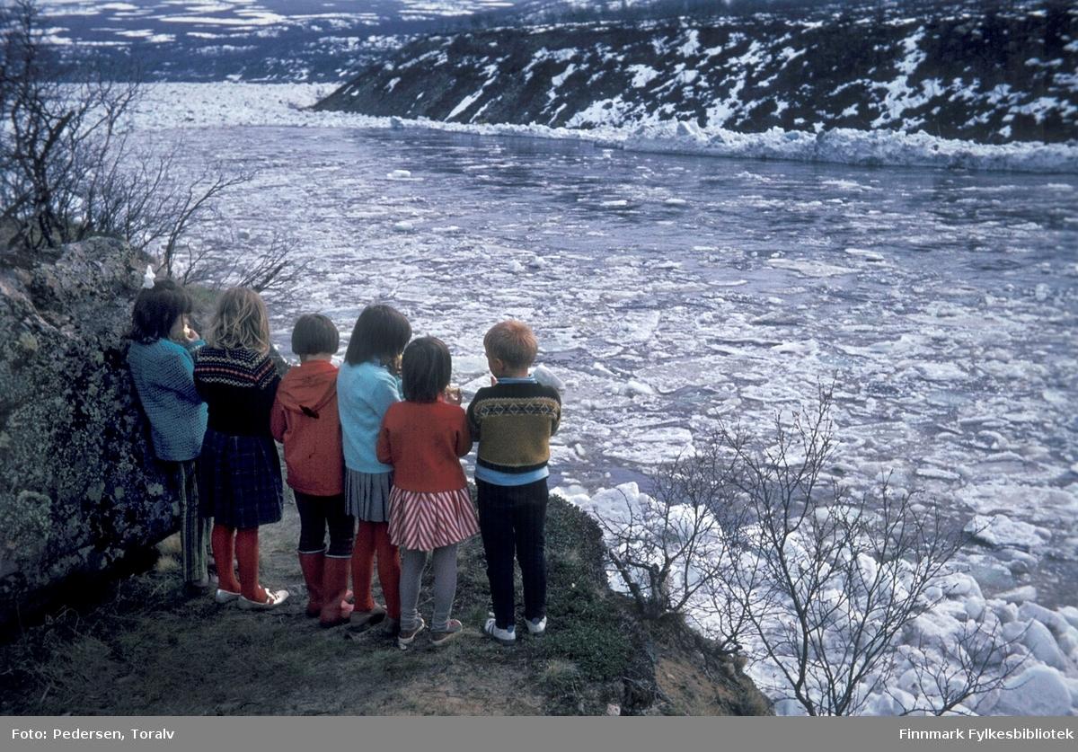 Isgangen i Tanaelva er en voldsom begivenhet og et mektig syn. Barn observerer isgangen i Sirma i mai rundt 1970. Bildet er tatt av Toralv Pedersen. Fylkesbiblioteket har 200 digitale kopier av Toralv Pedersens bildesamling, de fleste tatt i Sirma i periode 1966-1978.