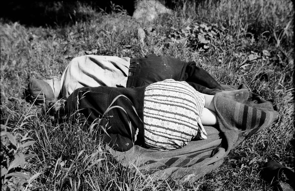 Ett par vilar i gräset på en filt. Det tycks vara lite kyligt för kvinnan har vikt upp filten över vaderna.