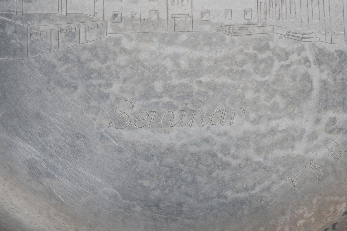 Bilde av en bygninger på både over og undersiden.  På oversiden: En hovedbygning med tverfløy og industrielle bygninger på den andre siden. Under står det skrevet Seminar, muligens her i betydningen av skole, da hovedbygningen kan ligne på et eldre skolebygg. Det har ikke lyktes å identifisere byggene nærmere. På baksiden: Øverst står det skrevet Oflag. Bak et piggtrådgjerde synes en fangeleir bestående av to lange brakker. I en enden en mindre brakke. Under står det: Luckenwalde.
