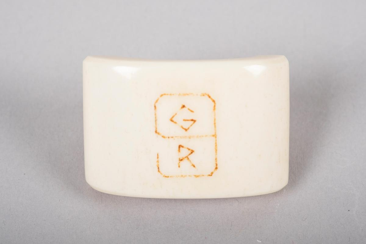 Serviettring laget av polert bein- eller hornmateriale med et buet frontstykke. Grinisymbolet er gravert inn i ringens frontstykke