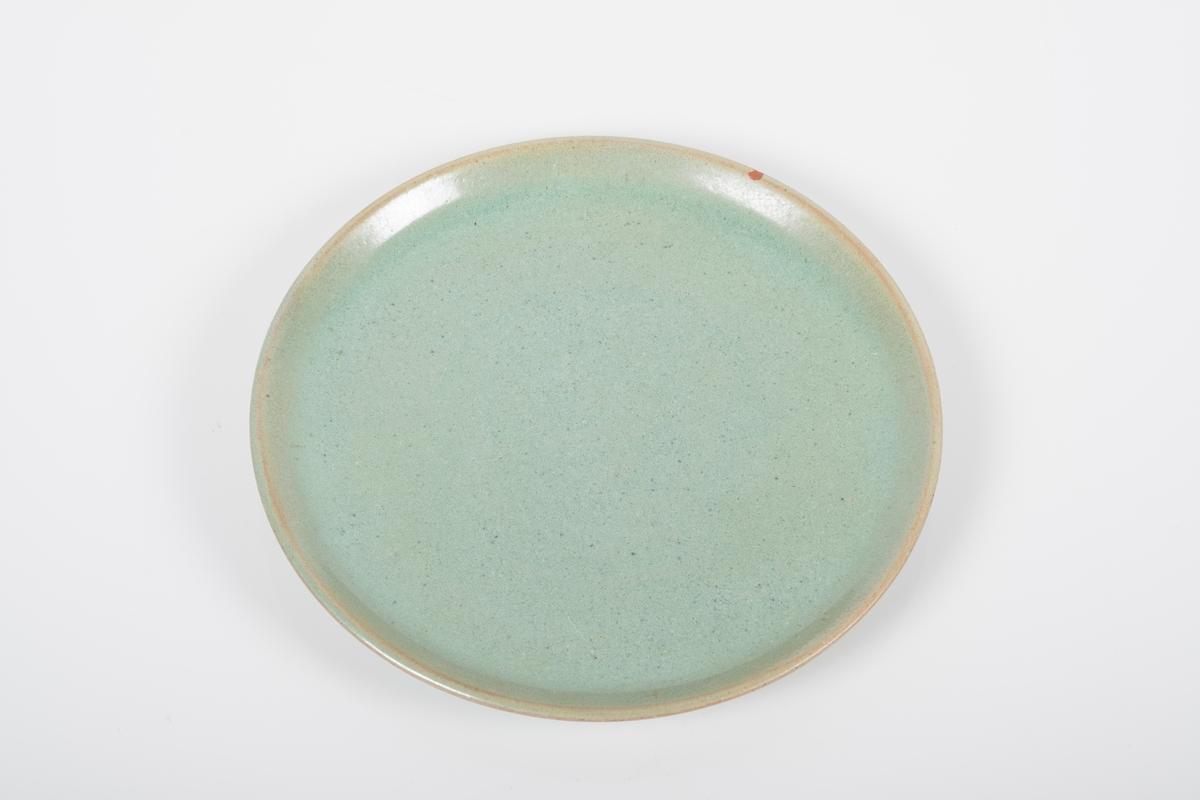Asjett i keramikk med grønn lasur. Blanke overflater. 5 små knotter på bunnen, usikker funksjon.
