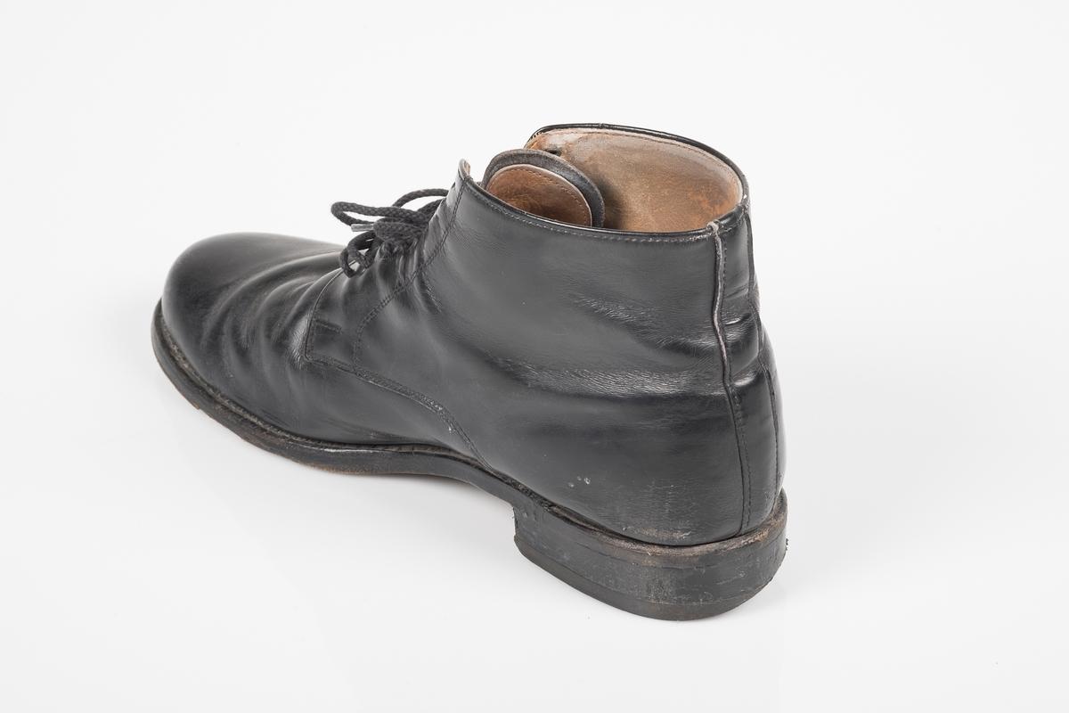 Høyre sko av et par svarte skinnsko med skolisser i bomull.
