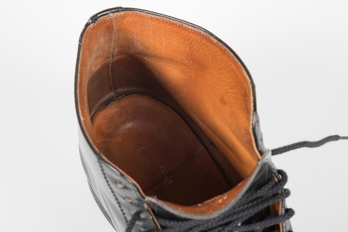 Venstre sko av et par svarte skinnsko med skolisser i bomull.