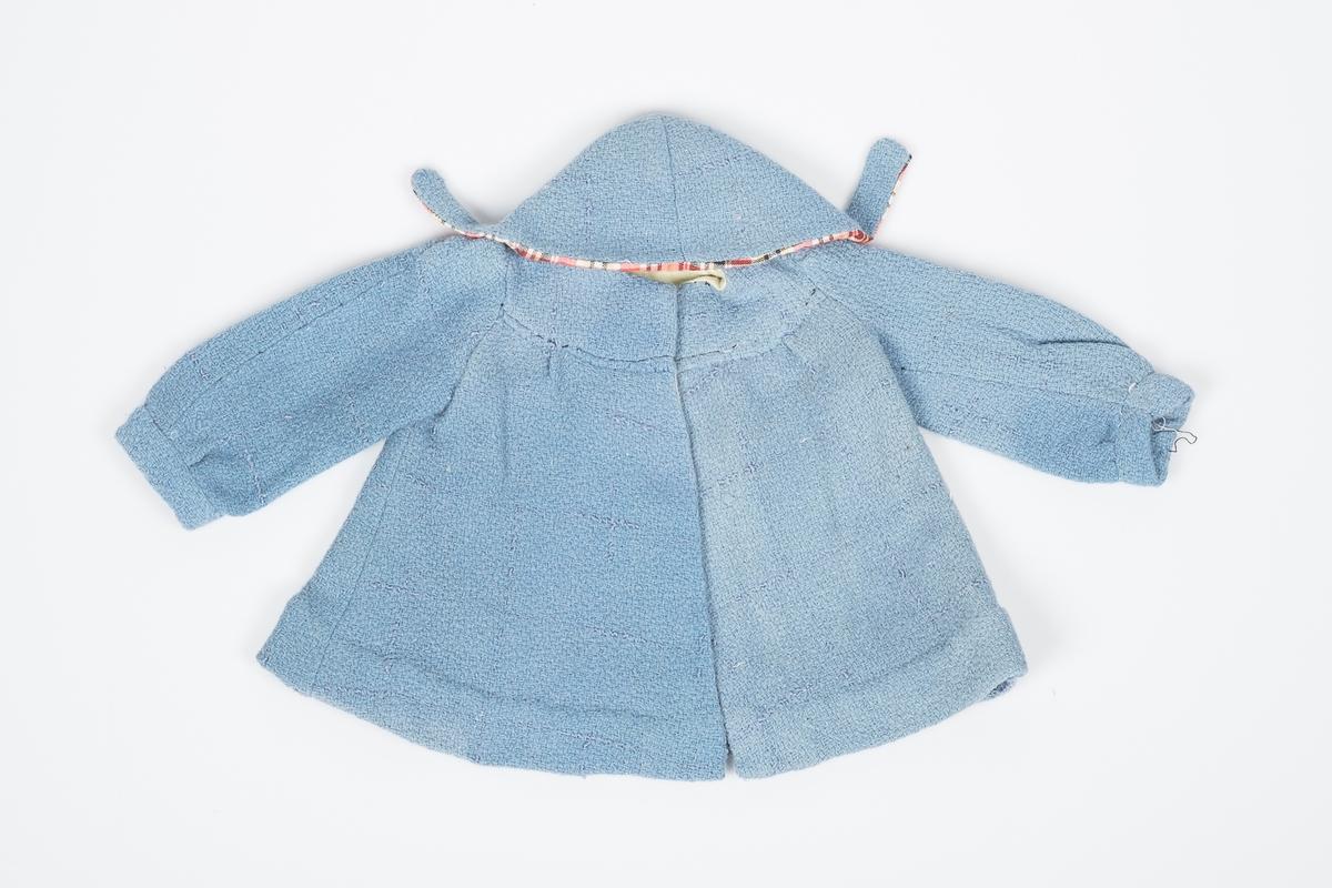 Lyseblå kåpe til dukke, fôret med grønt stoff i livet og rødrutete stoff i hetta. Kåpen ble nok godt brukt for den er ganske slitt.