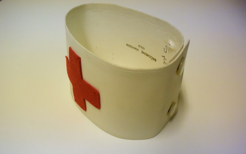 Stivet hvit armbind med rødt kors i filt eller ull sydd på. Festes rundt armen med to hvite knapper.