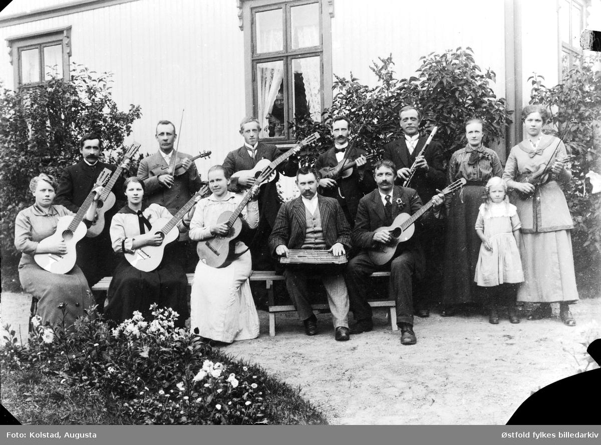 Gruppeportrett av musikkforening (?) utenfor våningshus. Musikantene har fiolin, gitar, fløyte og langeleik, kan det være religiøs forening? Alle personene er ukjente.