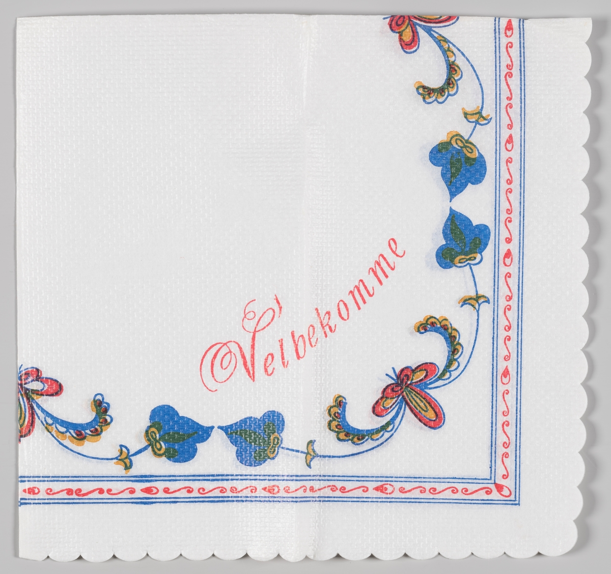 Rosemalte blomster innenfor en kantramme og reklameteksten Velbekomme (ukjent produkt).