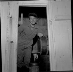 Bodø. Givær. Bu. En mann i arbeidsklær står i døra. Tapper v