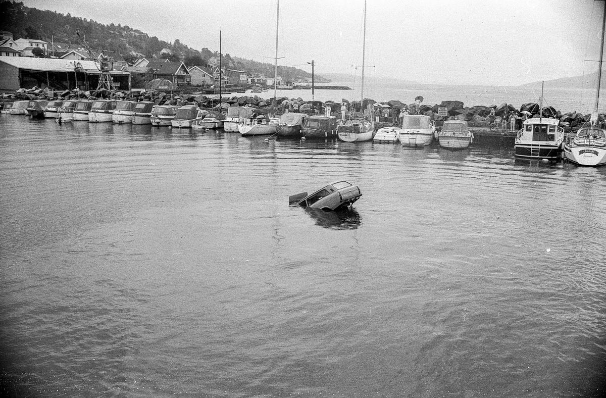 Bil ut i vannet i Drøbak båthavn. Øvelse med Frogn brannvesen og politi. Mange tilskuere med paraply.