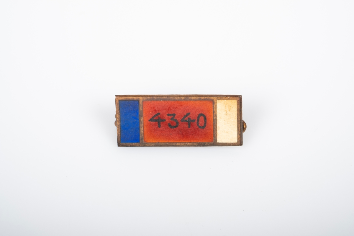 Nål med et fangenummer. Nålen har tre fargefelt; blå, rød og hvit. Fagenummeret er i det rød feltet. Materialet på nålen er trolig messing.