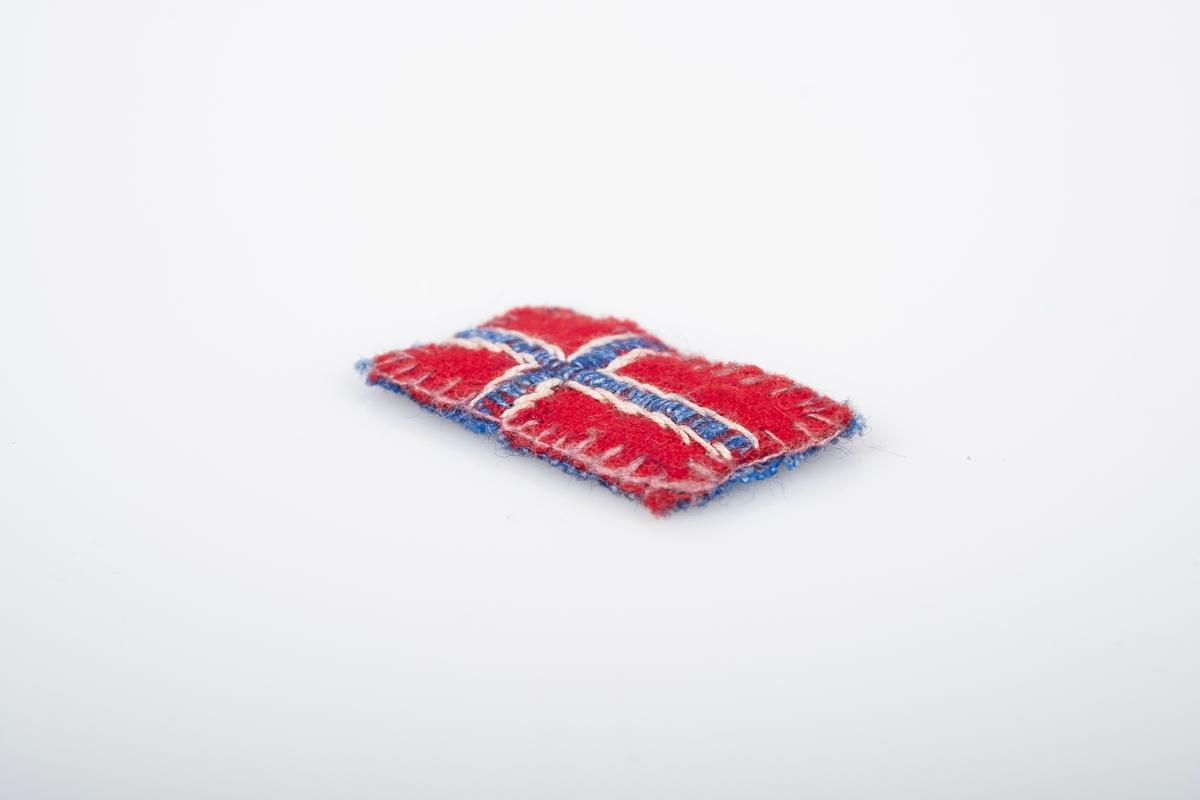 Et lite norsk flagg. Den er sydd og brodert på hånd. Den er sydd sammen av to stoffbiter, rød på forsiden og blå på baksiden. Det blå og hvite krysset på flagget er brodert.