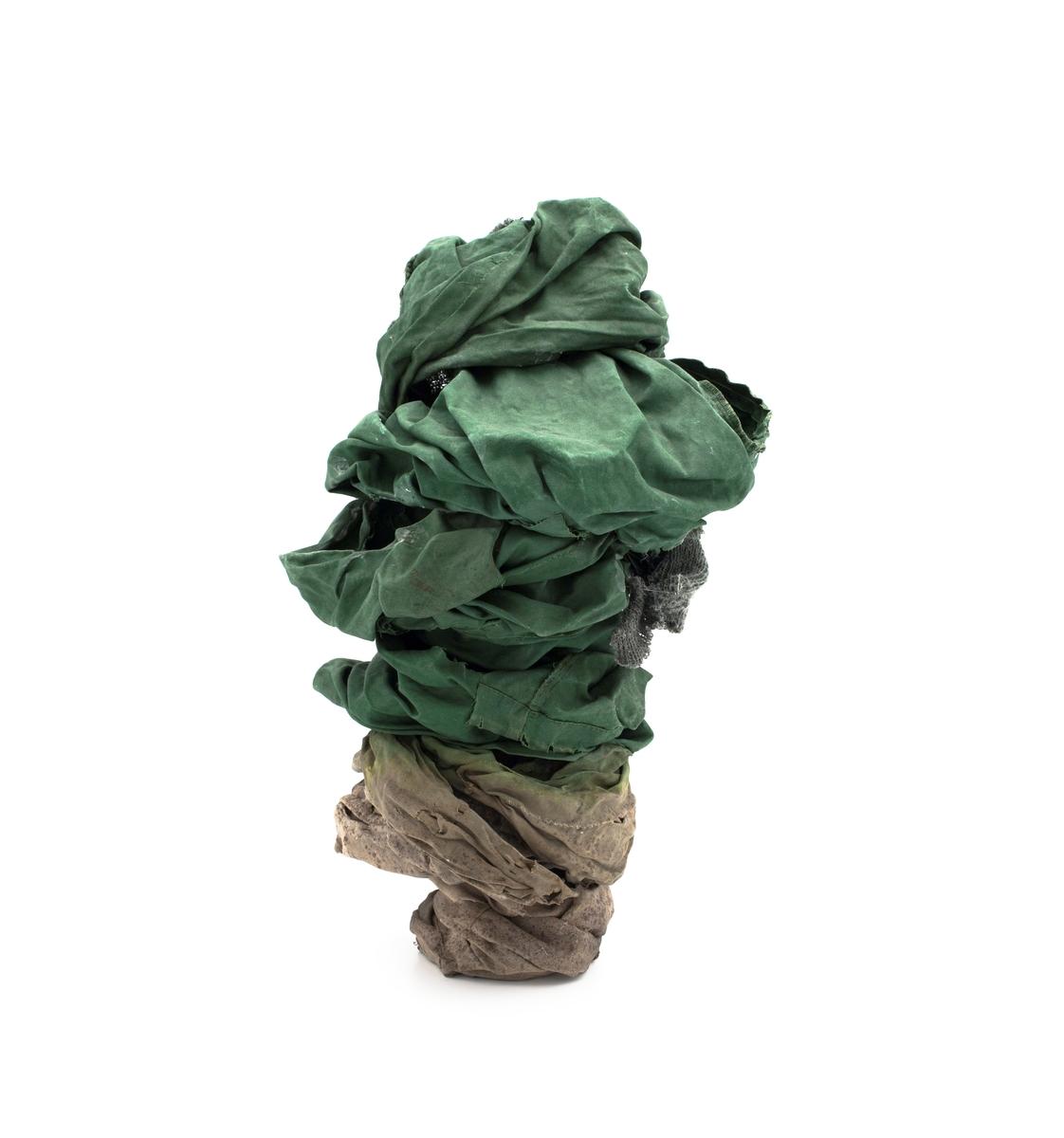 Tekstilt avfall i form av brukt tøy bygd opp i en abstrakt konisk form.. Tekstilene er i grønne og brune sjatteringer.  Kunstner opplyser om at rent teknisk er begge skulpturene bygget opp ved at tekstilene settes inn med lim som gjør at tekstilene blir harde når de tørker. Dette er en langsom prosess siden limet er tungt og må tørke helt mellom hvert lag med tekstil.