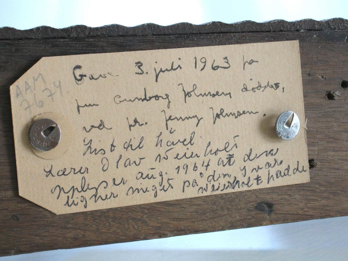 List til høvel. Eik, Brunbeiset. Flatt, langt stykke tre med en del spikerhull. Langs den ene overkanten påsatt en list av jern, med bølgende flate.  Jernbånd, ferrobetbehandlet, antag. i 1963-64.