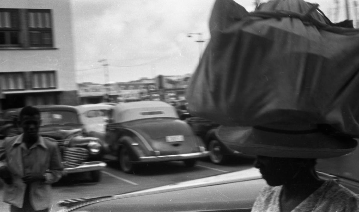 Transport av varer på hodet. Biler og havnen i bakgrunnen. Suderøy på vei til fangstfeltet.