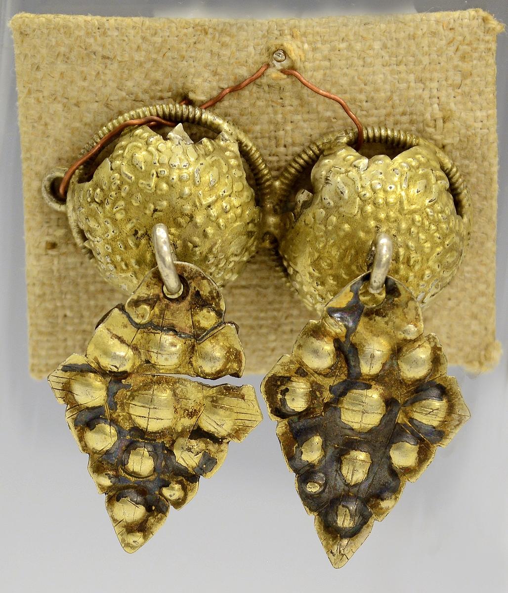 Malespenne av forgylt sølv med løv. Fra protokollen: 1 par tröiehegter, stjerneformet, med rhombeformete löv, hvorpaa buler.