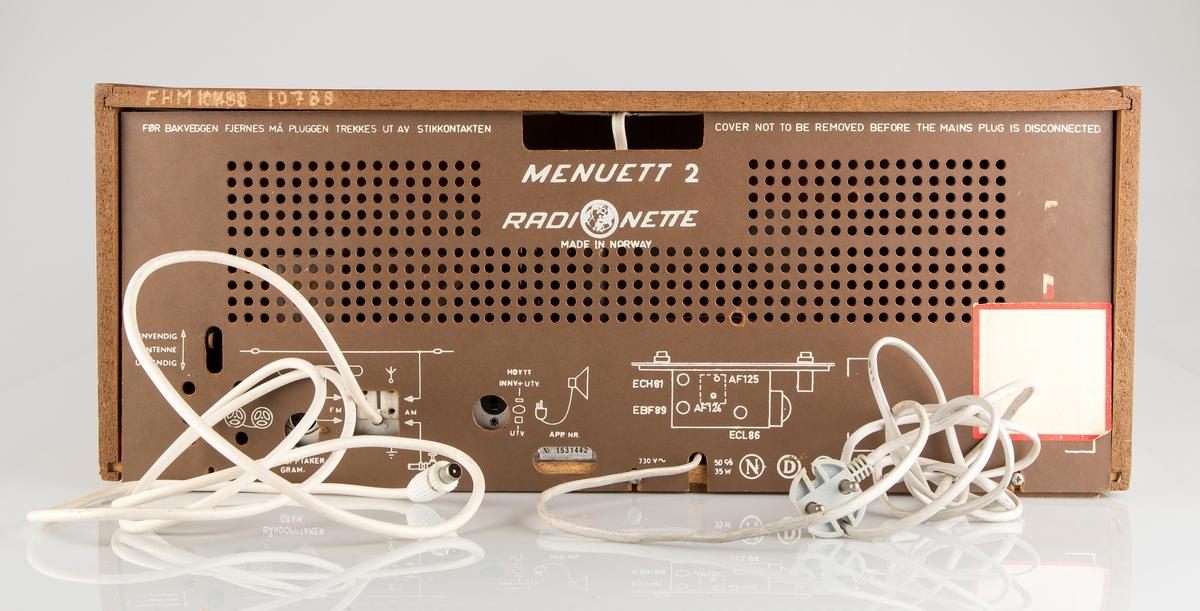 Rektangulært radioapparat med innebygd høyttaler på den ene siden. Teak-finert kasse, fast strømkabel, antennekabel med veggplugg.