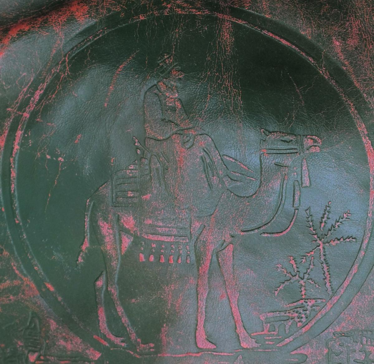Kamelsal, deler montert med skruer, hengsler m.m. Sal med preget mønster.  Preget mønster i skinn. Stanset mønster i blikk. Brun sal, grønn pute.