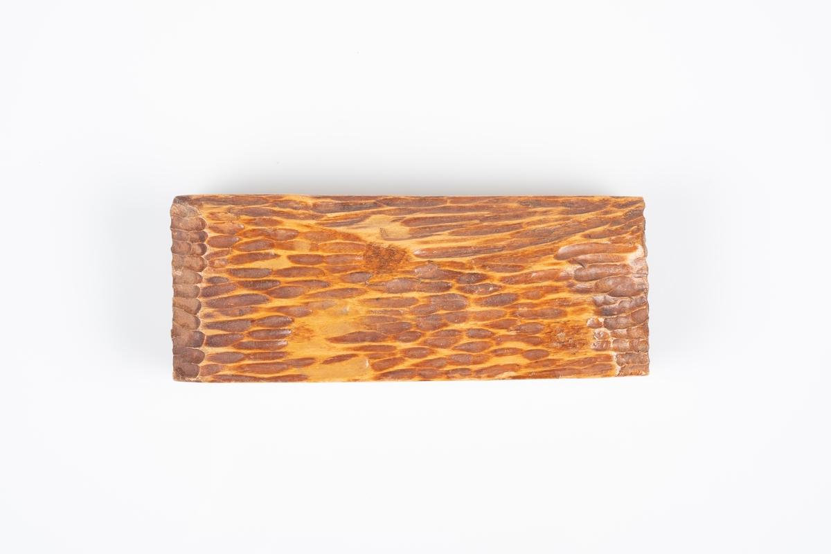 Et trestykke med utskjæring på oversiden og kortsidene så det skal ligne trebark. Det utskårede området er malt mørkt brunt. På den ene langsiden er det utskåret Grinisymbol.
