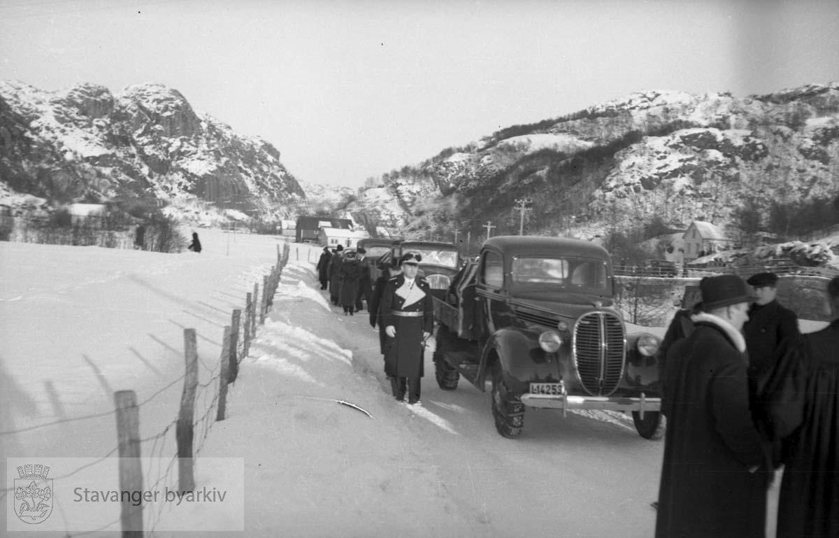 Fra Altmark-affæren i Jøssingfjord februar 1940..Gravfølge. Tysk offiser til venstre. Prest til høyre...14. februar 1940 kom det tyske hjelpefartøyet «Altmark» inn på norsk sjøterritorium utenfor Fosenhalvøya på hjemvei til Tyskland. Altmark hadde ca. 300 britiske krigsfanger om bord, og det fikk lov til å passere gjennom norsk territorialfarvann, eskortert av en norsk torpedobåt...Altmark ble oppdaget av et britisk fly samme dag, og britene tok opp jakten på skipet. Den britiske jageren «Cossack» avskar om formiddagen 16. februar Altmark og forsøkte å stoppe den. Altmark søkte tilflukt i Jøssingfjorden i Rogaland, beskyttet av den norske torpedobåten i fjordmunningen. Samme natt gikk Cossack inn i Jøssingfjorden og bordet Altmark, mot protest fra den norske torpedobåten...Det utspant seg en kort kamp, og seks tyskere ble drept og flere såret. Cossack befridde de britiske fangene og stakk til sjøs..