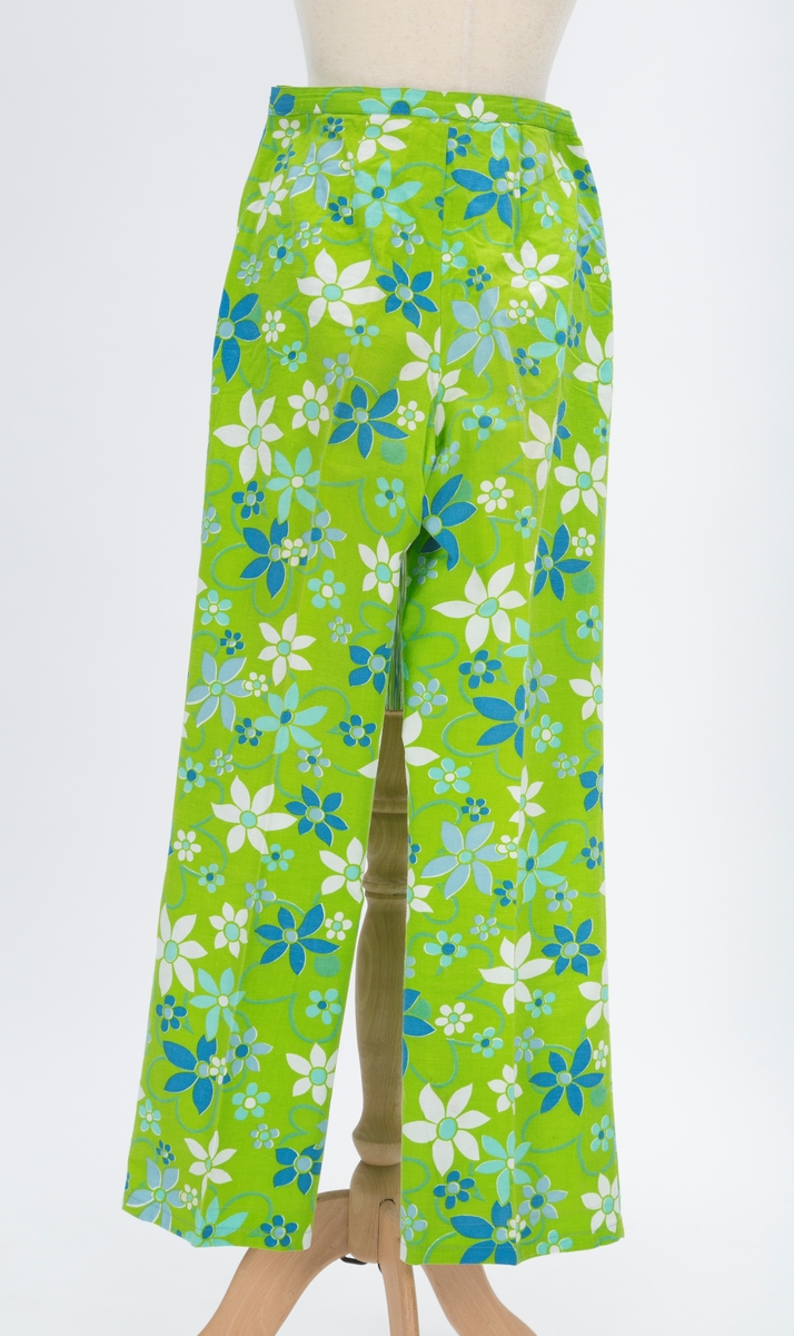 Todelt med et vilt blomstermonster. Buksen er rett. Overdelen kneppet foran , uten ermer og rund krage. Utepaasydde lommer