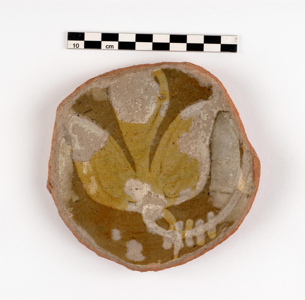 Del av kärl. Keramik: Yngre rödgods. Botten från fat. Hornmålat i grönt med växtdekor.