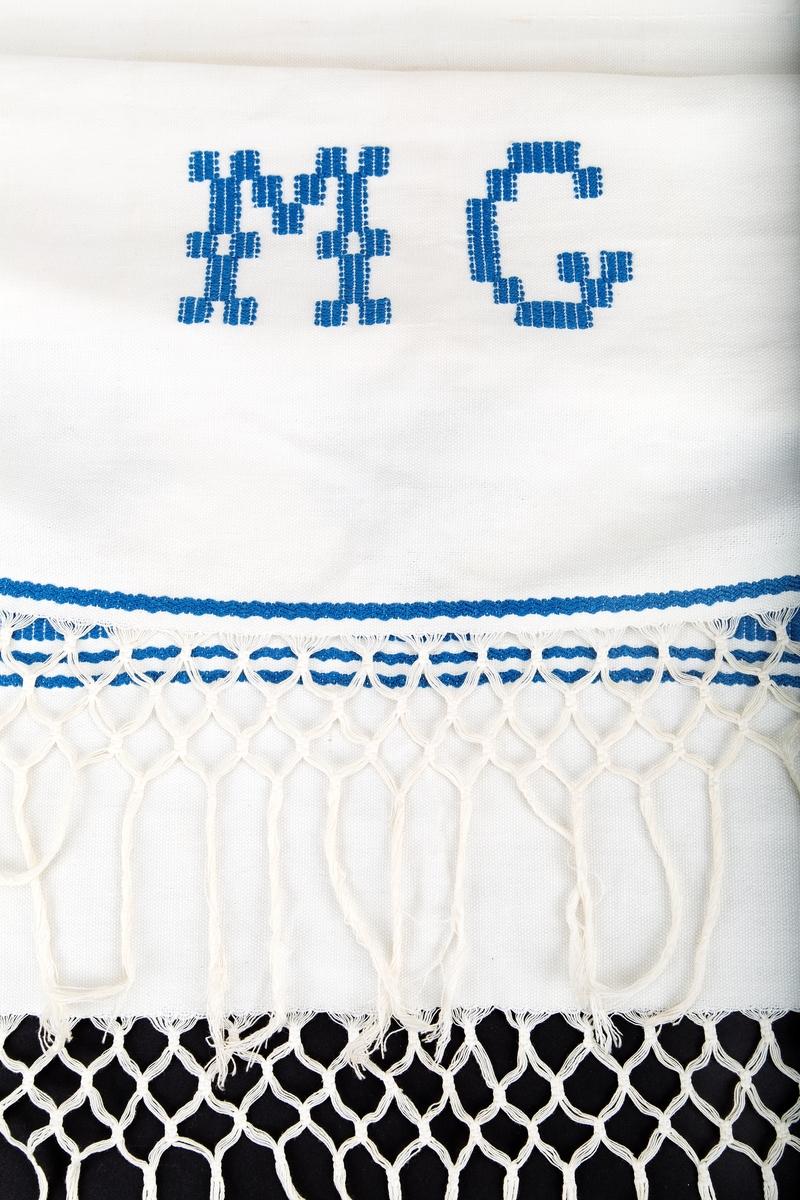 Håndvevd lin. Hvitt med blå innvevninger. Motuv: 3 stiliserte trær med en søyle på hver side. Ender i knyttede frynser