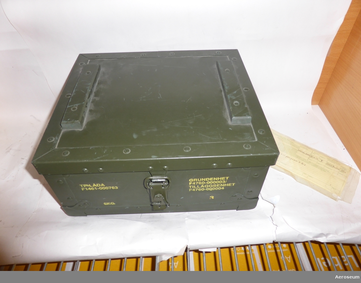En grundenhet för vindhastighetsmätare, i en grön transportlåda. I lådan finns det, utöver grundenheten, en plastpåse och ett papper med instuktioner på.