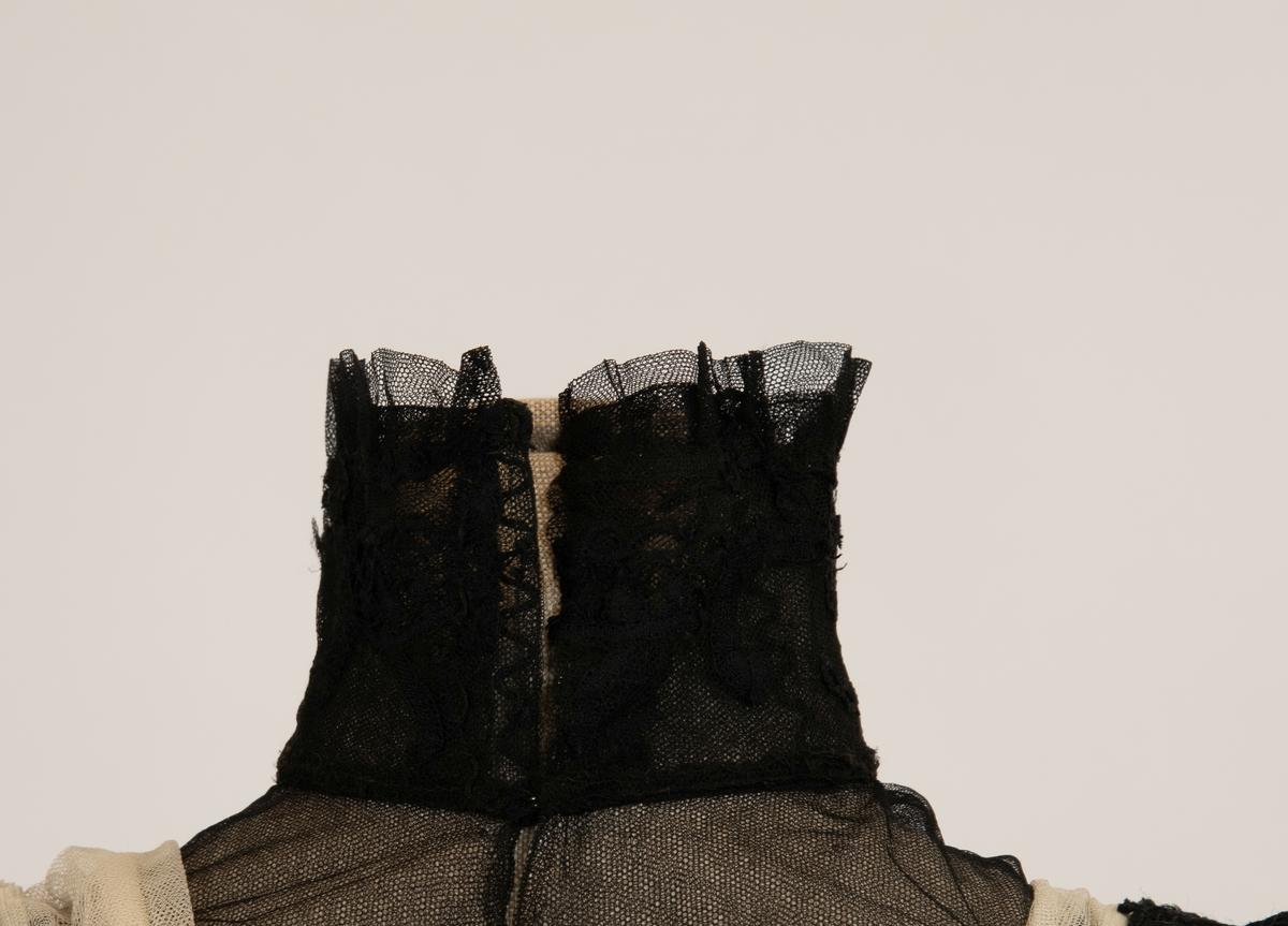 Selskapskjole.   Kort liv med et bredt belte av sort silkebånd med en  dobbeltsløyfe midt bak. Midt foran har kjolen en bred  tyllblonde  i full lengde, bred krage, firkantet, med pomponger og små  sløyfer.  Over ryggen to brede tyllblonder, lukket midt bak med  hekter.  I den firkantede utringning hvit tyll. Trange 3/4 ermer i  tynt hvitt stoff med sort tyll over. Skjørtet er utskrådd med  slep,  underskjørt av sort taft med tynt sort silkestoff på  utsiden,  nederst er. plissert kant. Sort silke, to sorter sort tyll, tyllblonder, sort taft, hvit tyll.
