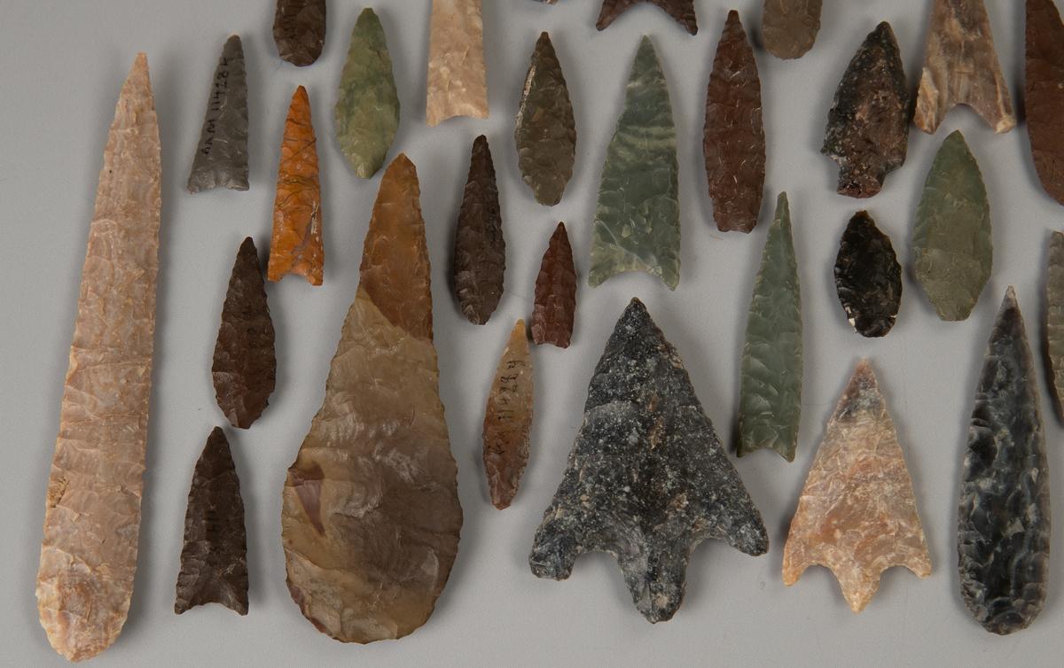 A) Lys grårosabrun stein,  på den ene side lysere flekker.  Rundet i den ene ende, avsmalnende  og spiss i den andre. B) Gråbrun og brun (brun spiss).  Bred dråpeformet spydspiss.   C)L. Skifergrå flint.  Bred trekant med to U-formede  innskjæringer i øvre del.