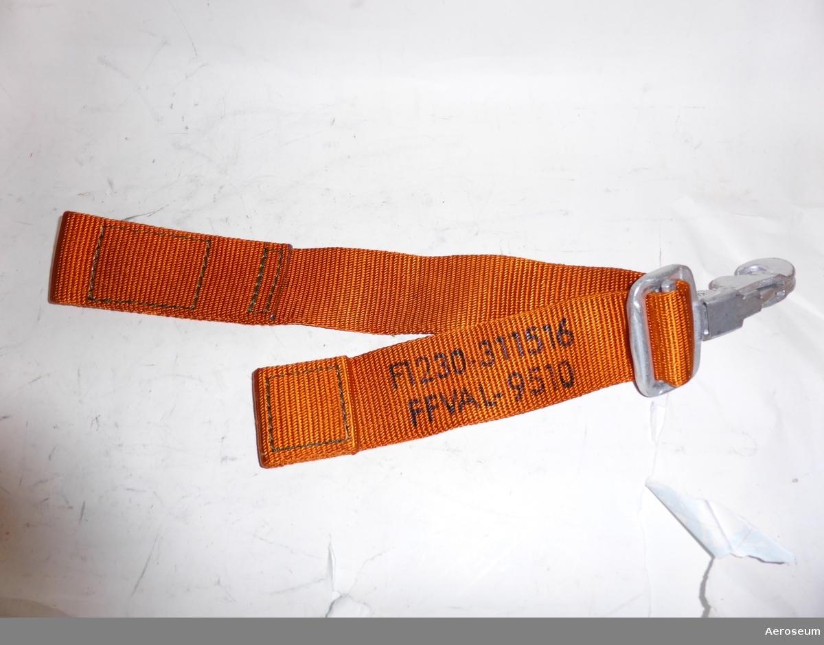 """En fastbindningsrem för helikopter. är orange och i svart text står det på den: """"F1230-311516 FFVAL-9510"""". Har även en metallhake."""