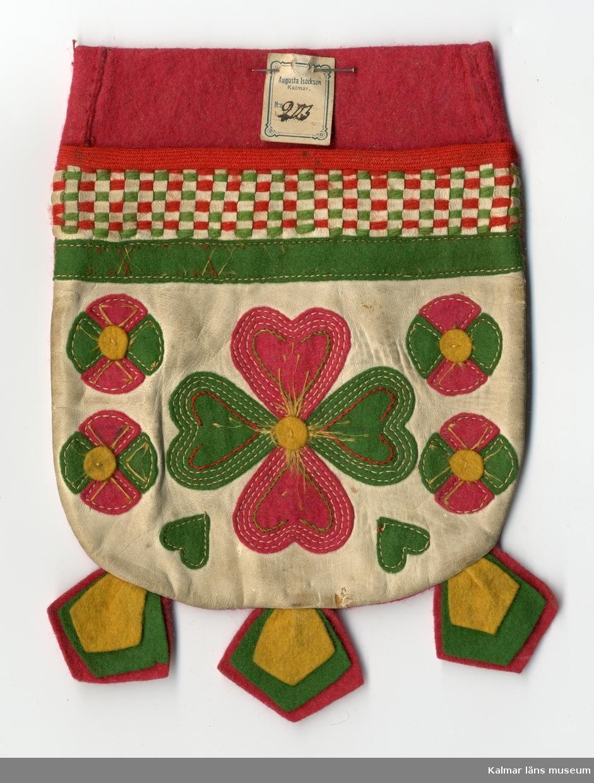 KLM 28082:409 Ficka, kjolväska, kjolsäck eller kjolficka av textil, ylle och skinn. Ficka, baksida röd, framsidan av skinn, vit, rikt med garneringar i filt, rött och gult, garneringar i filt i stilistiska mönster av hjärtan och blommor.. Framsida, upptill, två bårder, en  i rutmönster, av yllegarn, grönt och rött, trädda i skinnskåror, och en bård av filt, grön, med flätsöm på. Flikar, nertill, under fickan, tre fastsydda flikar med tre olika stora filtbitar i rött, grönt och gult. Tillbehör till  nationaldräkt.  Lapp, av kartong, fäst vid öppningen på fickan med förtryckt text: Augusta Isackson Kalmar No, handskrivet, nr: 203, Numret är ett varunummer i Augusta Isacksons försäljning och i hennes priskuranter. (KLM028082:384-386)