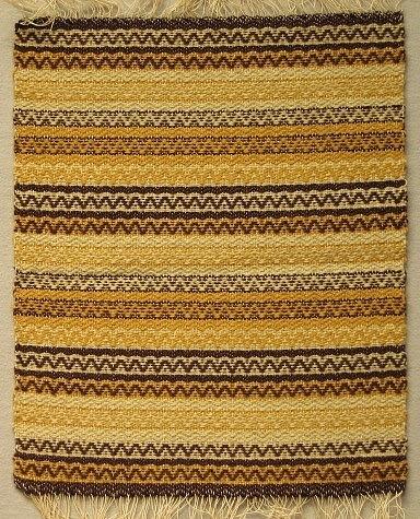 Dukprov med  frans. Grå botten med mönsterränder i gult och brunt.Varp: lingarnInslag: ullgarn Under 2:a världskriget (kristid) fick industrifärgat garn endast användas till nyttovävar. Därför vävdes det mycket med ofärgat och växtfärgat garn.Hos väverskorna var det populärt att väva dessa ylledukar då det var ont om arbete och de gav bra betalt, 1.75 kr per meter.Hemslöjden fick då och då under denna period besök av kontrollanter (från statlig myndighet?)  som kom för att se efter att reglerna för användningen av färgade garner efterlevdes.