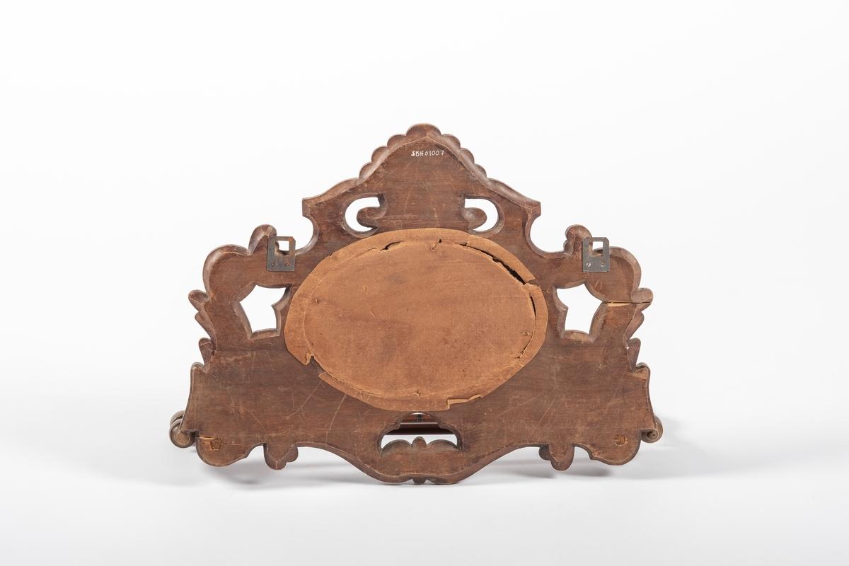 Selve speilet er ovalt. Sitter i en ramme av tre, dekorert med skjell eller vifte over speilet, og ellers fantasiblader (ant. akantusinspirert), rutemønster og blomster.To dreide tretapper sitter festet til trerammen, en på hver side. Gjennom disse går det en lang, rund pinne, hvis ender er festet til hver sin profilerte trepinne. Disse tverrpinnene danner feste for nok en trestang, som sitter lenger ut. Denne konstruksjonen av trestenger kan slåes sammen. I den ene runde stangen er det skrudd inn to kroker, som antagelig er av nyere dato. Baksiden av speilet er dekket med papp, og lenger opp er det skrudd på to metallfester (for oppheng på vegg).