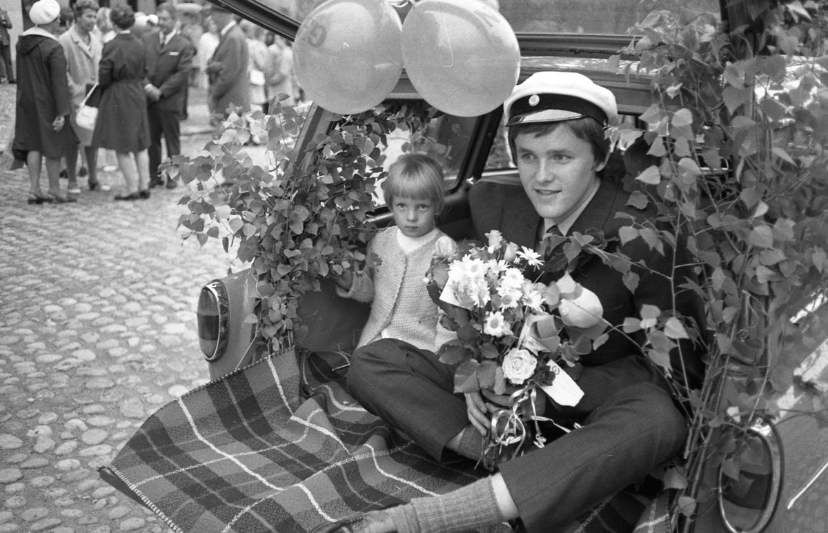 Studentdag! I lövad och ballongförsedd baklucka åker Bertil Pell tillsammans med en liten flicka. Bertil har studentmössa och famnen full av blommor.