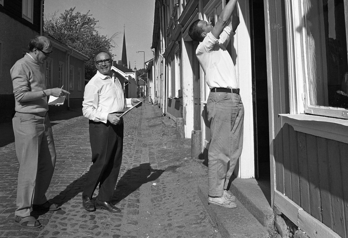 Bertil Levin och Yngvar Gunnarsson ställer iordning en diversehandel på Västerlånggatan. Här intervjuas de av reporter Tomas Laghé från Nerikes Allehanda. I bakgrunden ses tornet på Heliga Trefaldighetskyrkan.
