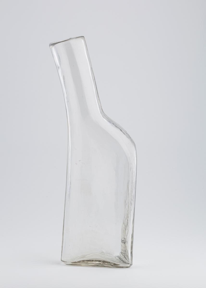 Bekkenet er en avlang flaske med tre kanter og langsgående grunnflate, dvs. at flasken ligger. Fra den ene kortenden stikker det en tut med en vid åpning ytterst. Den står skrått på flasken.