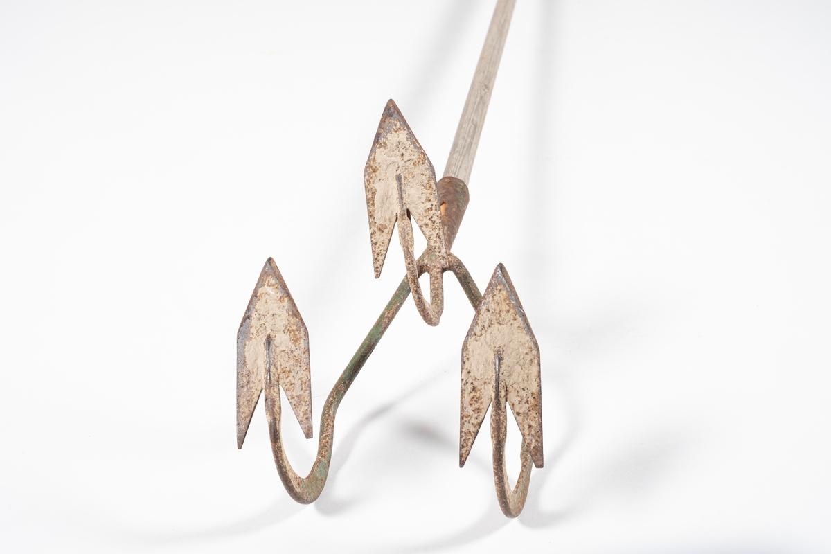 Langt, smalt skaft med hode med tre buede tinder. I enden av tindene er det hakkeblader. Den midterste tinden er kortere enn de andre.