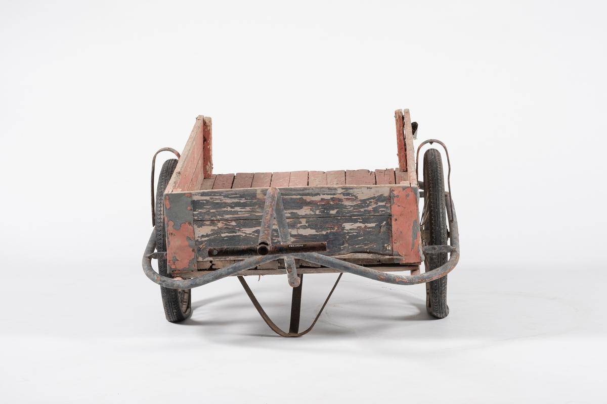 Tralle på to gummihjul. Rektangulær kasse dannet av liggende plank, en manglende kant på kortende. Metallforsterkning på alle hjørner. Understell dannet av  bøyde jernrør, hvor ett danner håndtaket. Tverrliggende jernrør til håndtering.