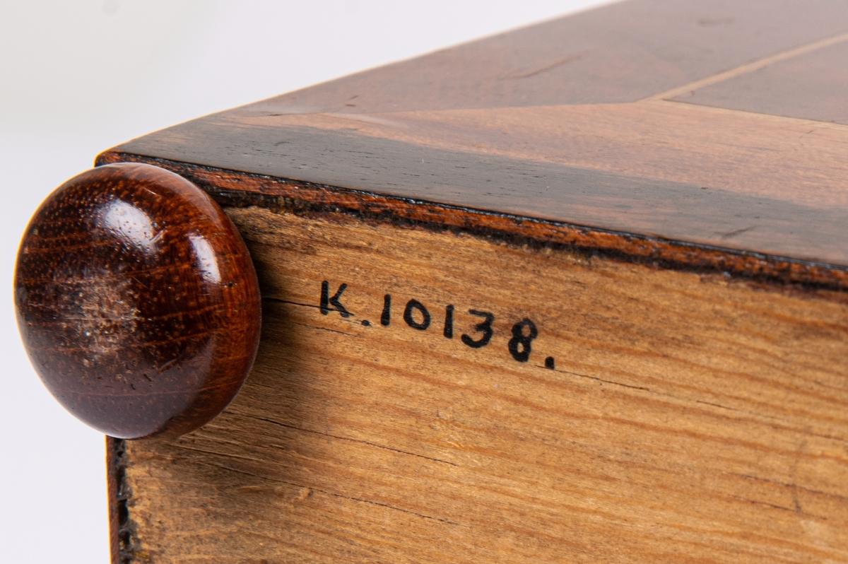 Kat.kort: Syskrin, mahogny, på låga kulfötter, inlagd oval figur på locket. Nyckelskylt av ben.