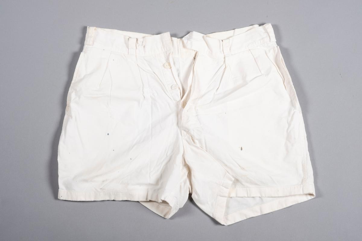 Hvit shorts med lommer i siden og knepping i front. Shortsen kneppes med 5 knapper. Den øverste knappen mangler. Shortsten har smygstoler for bruk av belte. Det er sydd folder i front.