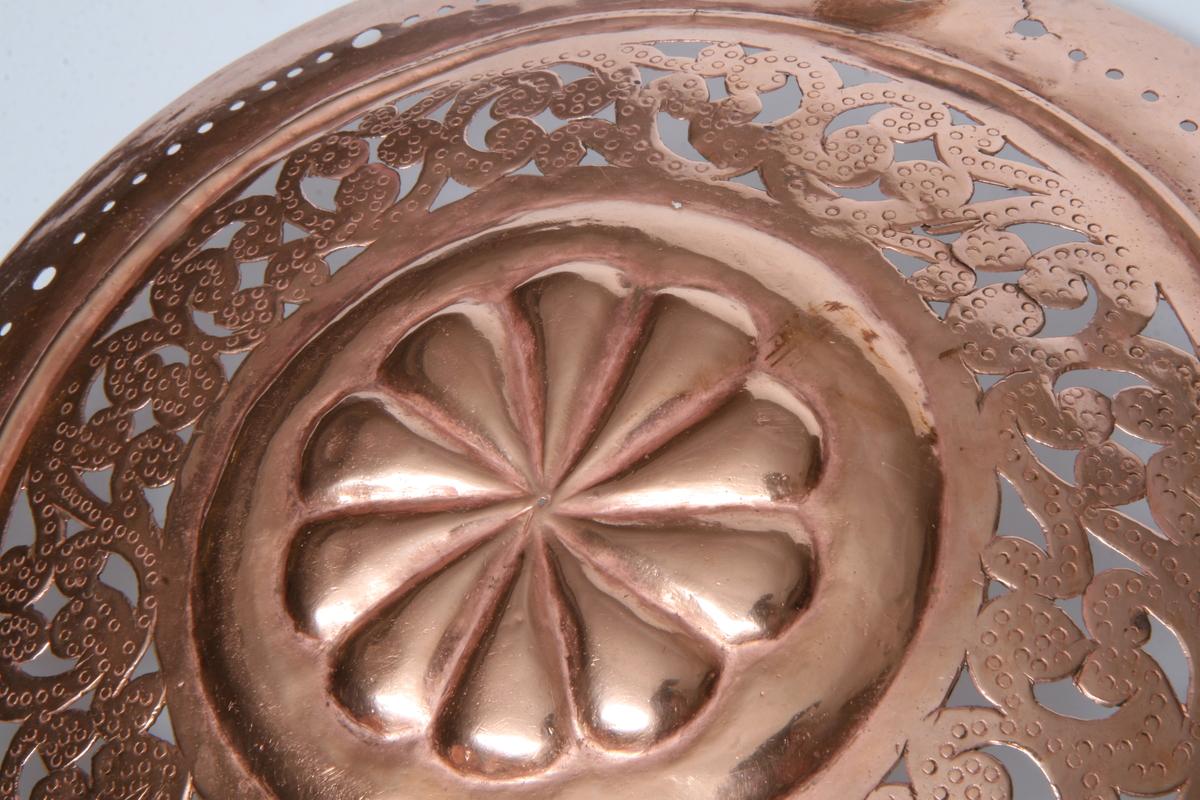Drevet (og siselert?) kobber, i midten en rosett omkranset av gjennombrudt rankeverk, lysarm med to holdere.