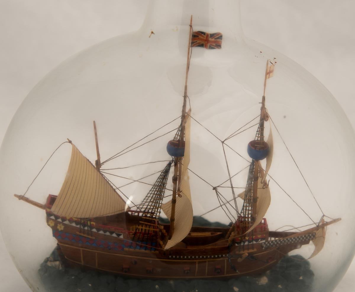 """Flaskeskute; """"Mayflower"""", en tremastet galleon fra 1615 , tok i l620 102 utvandrere fra England til Amerika. Symbol for frihetsrettigheter og religiøs toleranse.  Kuleformet glassflaske. Brunt skrog , dekorert i akterspeilet med border i blått , rødt , sort , hvitt og gult. Britisk flagg."""