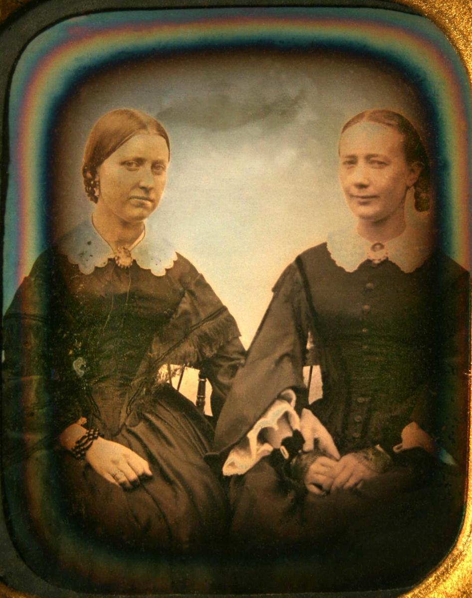 To sittende kvinner. Portrett av Laura Larssøn (f. 17/2 1830 i Bratteklev - d. 1908) og Edeline Anette Larssøn (f. på Torjusholmen 22/10 1834 - d.1915 på Merdø).    Tv. sittende kvinne med glatt tilbakestrøket hår med midtskill, flette i nakken, mørk kjole som går ned i spiss midt foran, hvit krave, ermer med et frynset kast over. Hvit blondekrave med kamé.   Th. sittende kvinne, glatt hår med midtskill, flette sees th., sort forknappet kjole med fløyelsbånd, hvit blondekrave med kamé, meget vide ermer med hvitt stoff i ermeåpningen.