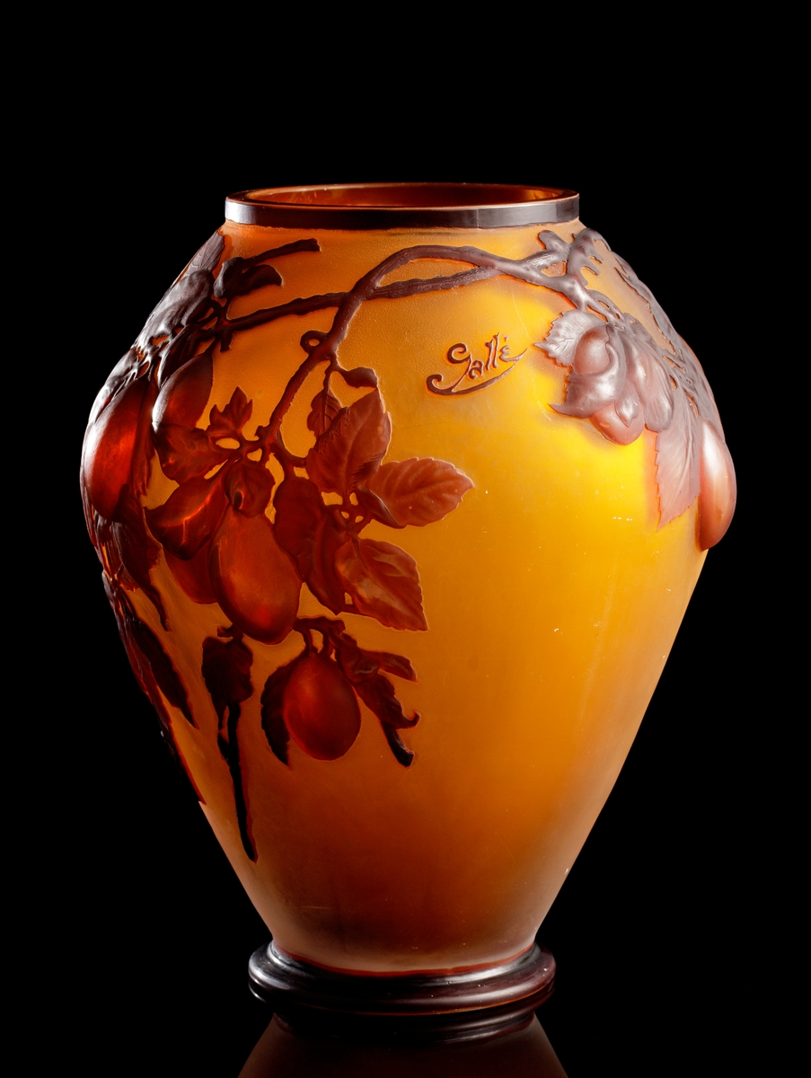 """Halvopak vas i gulbruna nyanser. Växtmotiv i etsat rödbrunt överfång skildrande grenar med frukter och löv. Enligt museets registerkort fanns tidigare en etikett från """"Löfbergs"""" där det stod skrivet """"G 13"""" eller """"G 131""""."""