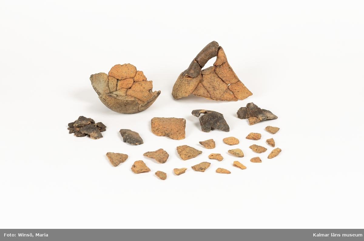 KLM 12654:1 Kärl, rörhänkelkärl, stort antal delar, varav några delar är ihoplimmade. Rörhänkelkärlet dateras till yngre romersk järnålder-folkvandringstid.
