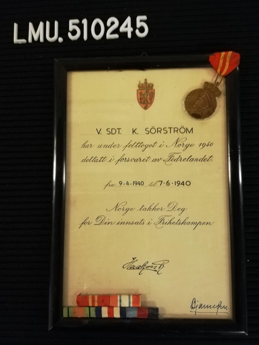 Diplom gitt til V.SDT. K. Sørstrøm for deltagelse i forsvaret av fedrelandet under felttoget i 1940. Diplomet er signert av kong Haakon 7. Diplomet er innrammet.