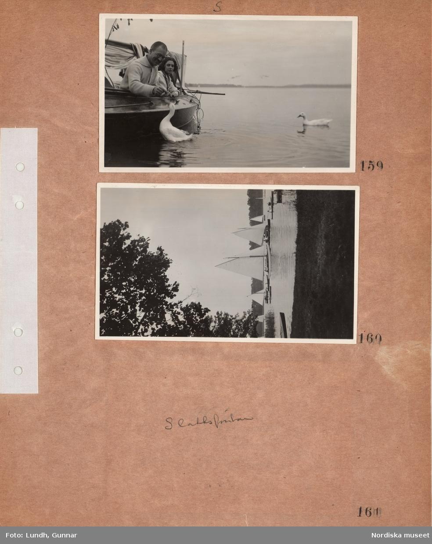 """Motiv: Utlandet, Berlins Omgivningar 157 - 177 ; En man och en kvinna sitter i en båt och matar en svan, vy över en sjö med segelbåtar och kanoter, anteckning på kontaktkarta 161 """"Slottsfontän""""."""