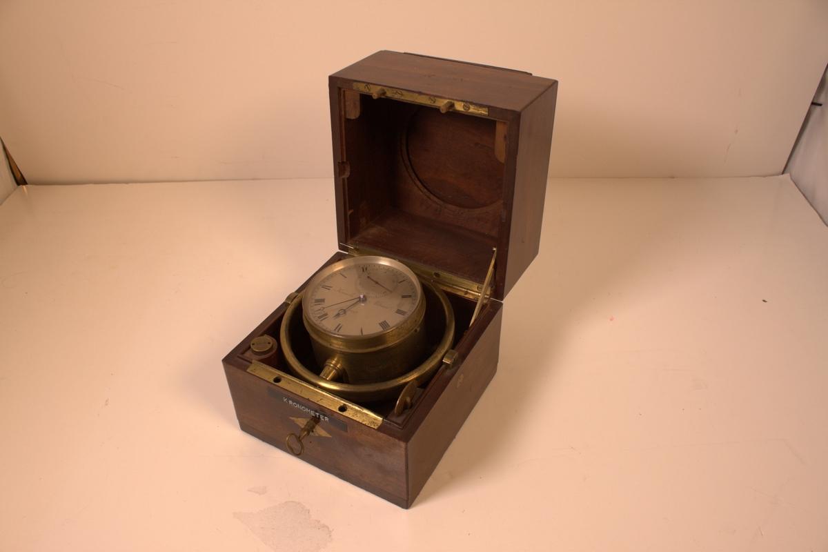 Kronometeret er utført i messing.  Det er glass over urskiva. Urskiva er hvit med sorte romertall. Sekundviseren har arabertall. Viserne har dypblå farge. På urets underside er det hull for opptrekk. Kronometeret er opphengt i kasse ved kardangopheng i messing. Kassa er utført i tre. Den har lokk med lås og nøkkel for tilgang til kronometeret. Oversiden av dette lokket har skyveklaff for åkunne se ned på urskiva. I kassas tre hjørner er skrue og to nøkler - en av disse er for opptrekk av kronometeret. Kassas mål mål: L 15 cm, B 15 cm, H 15,7 cm. Navigasjonsvesenet anskaffet dette kronometeret i 1835.