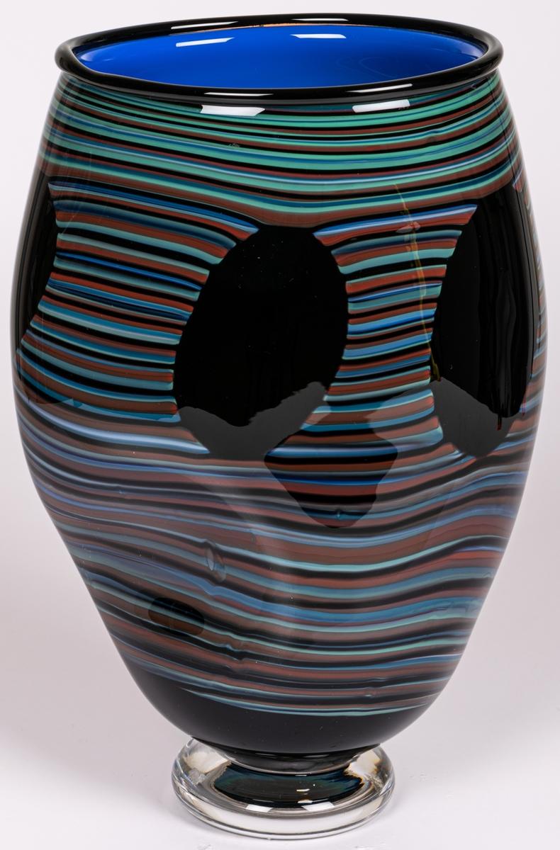 """Vas, blåst, med pålagda trådar, modell """"Salamander"""". Tillplattat oval. Tvärrandig i svart, brunt, blått och blågrönt med tre stora, ovala, svarta fläckar. Smal, tjock fot. Märkt under: """"Utställning""""."""